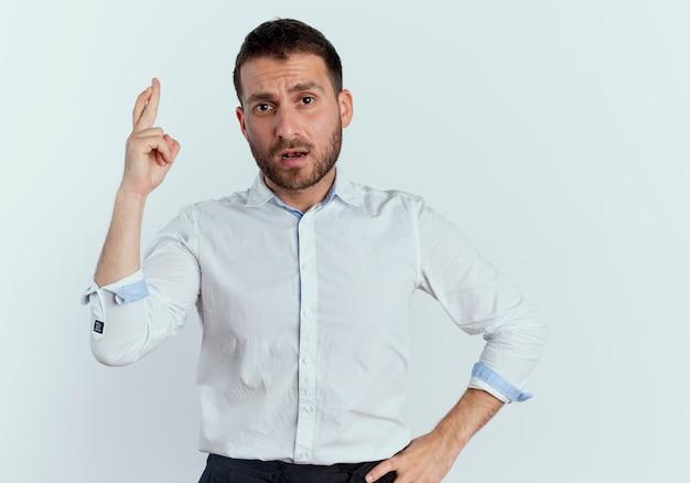 자신감이 잘 생긴 남자가 손가락을 교차하고 흰 벽에 고립 된 허리에 손을 넣습니다.