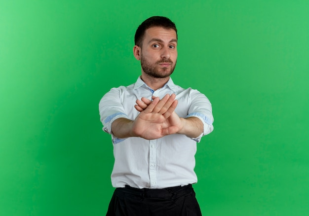 Confident handsome man crosses hands gesturing no isolated on green wall