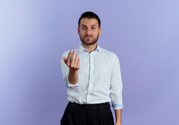 Уверенные жесты красивого мужчины приходят сюда, знак руки, изолированные на фиолетовой стене