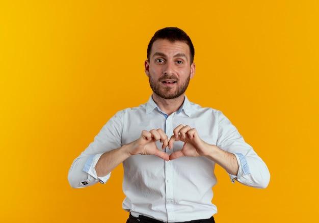 自信を持ってハンサムな男は、オレンジ色の壁に分離されたハートの手のサインをジェスチャーします。