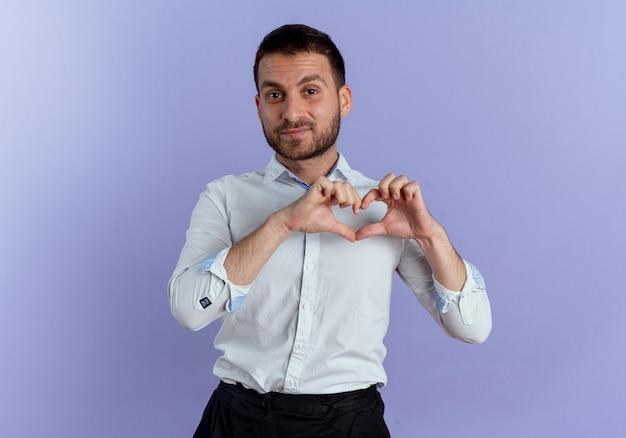自信を持ってハンサムな男は紫色の壁に分離されたハートハンドサインをジェスチャー