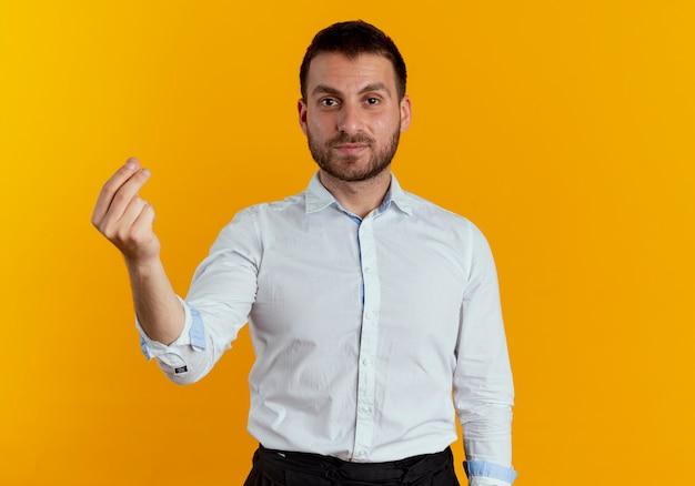 Fiducioso bell'uomo gesti soldi mano segno isolato sulla parete arancione