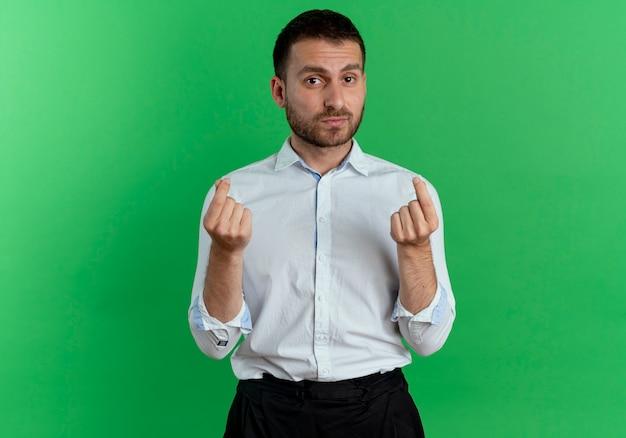 Fiducioso bell'uomo gesti il segno della mano dei soldi con due mani isolate sulla parete verde
