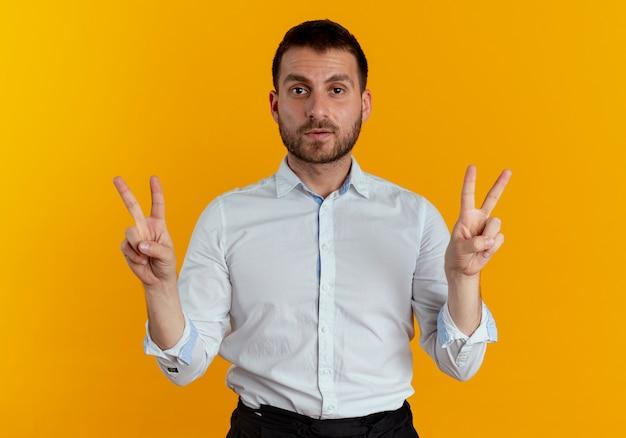 Fiducioso bell'uomo gesti il segno della mano di vittoria con due mani isolate sulla parete arancione