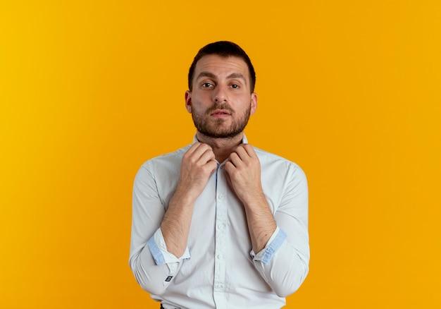 자신감이 잘 생긴 남자는 오렌지 벽에 고립 된 두 손으로 칼라를 보유
