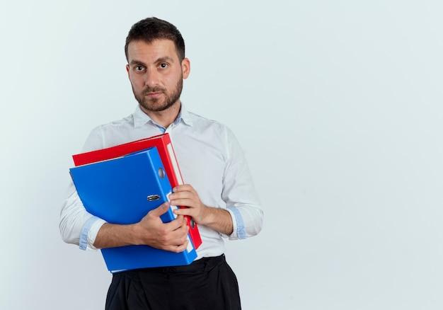 自信を持ってハンサムな男は白い壁に隔離されたファイルフォルダーを保持します。