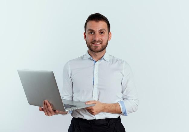 L'uomo bello sicuro tiene il computer portatile isolato sulla parete bianca