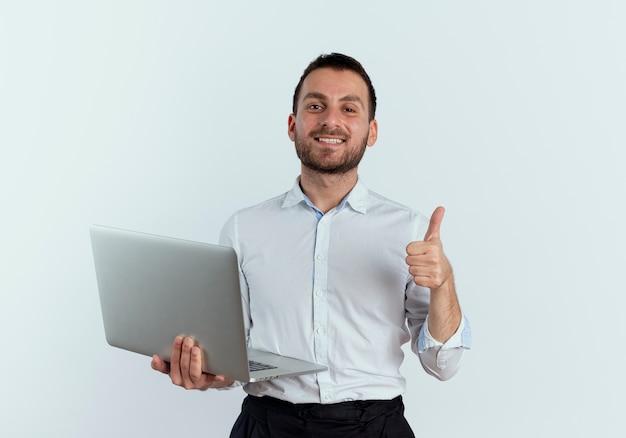 自信を持ってハンサムな男は白い壁に隔離されたラップトップの親指を持ち上げます
