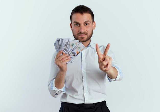 Fiducioso bell'uomo tiene soldi e gesti il segno della mano di vittoria isolato sul muro bianco
