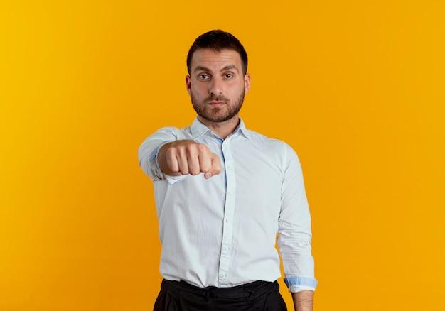 自信を持ってハンサムな男はオレンジ色の壁に隔離された拳を差し出します