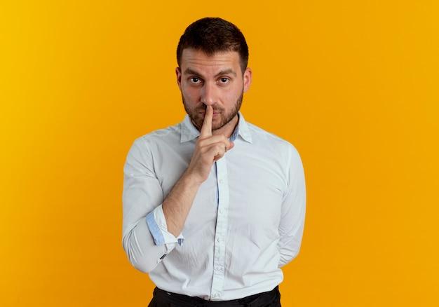 自信を持ってハンサムな男は、オレンジ色の壁に隔離された静かな静けさを身振りで示す口に指を置きます