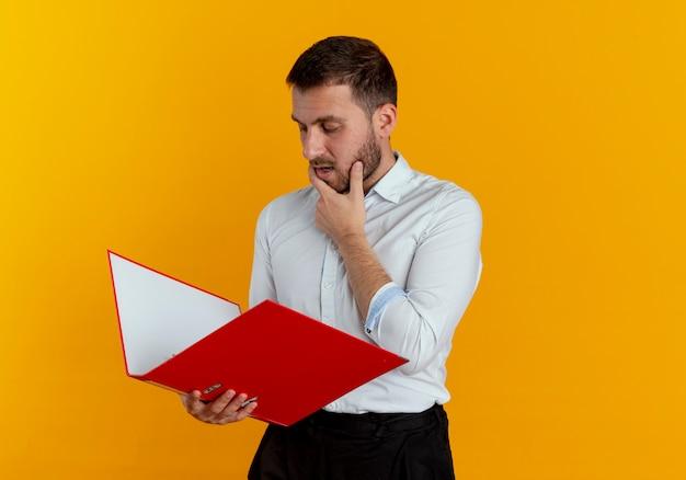 自信を持ってハンサムな男はオレンジ色の壁に分離されたファイルフォルダーを見てあごに手を置きます
