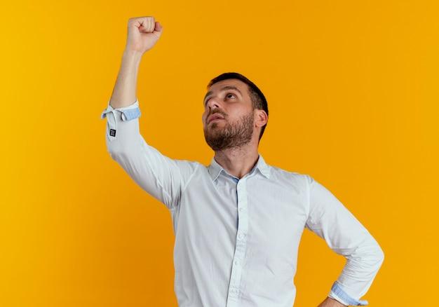自信を持ってハンサムな男は拳を上げ、オレンジ色の壁に孤立して見上げる
