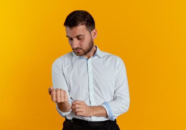 자신감이 잘 생긴 남자는 오렌지 벽에 고립 된 소매를 롤업