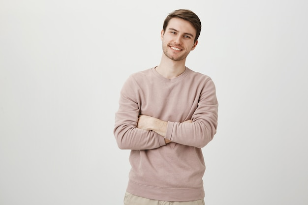 Confident handsome man smiling pleased, cross arms chest