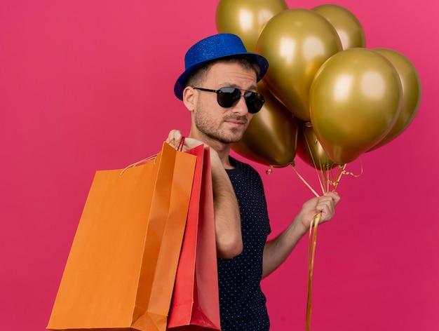 Fiducioso bell'uomo in occhiali da sole che indossa il cappello blu del partito si trova lateralmente tenendo palloncini di elio e sacchetti di carta isolati sul muro rosa