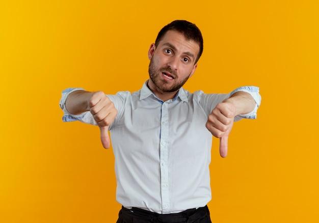 Уверенный красавец показывает палец вниз двумя руками, изолированными на оранжевой стене
