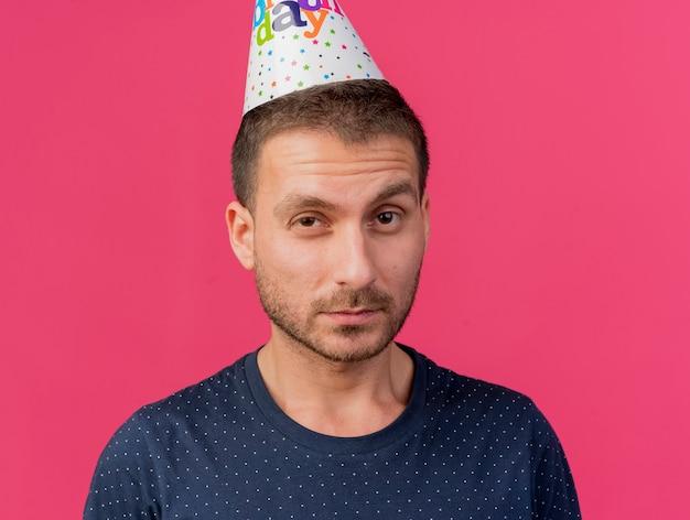 Fiducioso bell'uomo che indossa il cappello di compleanno guardando la parte anteriore isolata sul muro rosa