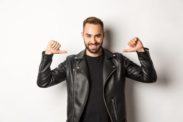 Уверенный красивый мужчина в черной кожаной куртке, указывая на себя и самоуверенно улыбаясь, стоя