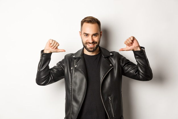 Confident handsome man wearing black leather jacket, pointing at himself and smiling self-assured, standing