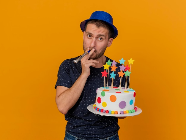 青いパーティーハットを身に着けている自信を持ってハンサムな男は、コピースペースでオレンジ色の壁に分離された笛を吹く誕生日ケーキを保持