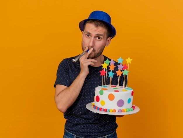 Fiducioso bell'uomo che indossa il cappello blu del partito tiene la torta di compleanno che soffia il fischio isolato sulla parete arancione con lo spazio della copia