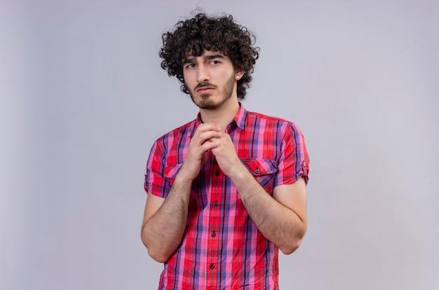 Un bell'uomo fiducioso con i capelli ricci in camicia controllata che tengono le mani insieme