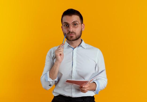 Fiducioso bell'uomo con occhiali ottici mette la penna sul viso e tiene il taccuino isolato sulla parete arancione