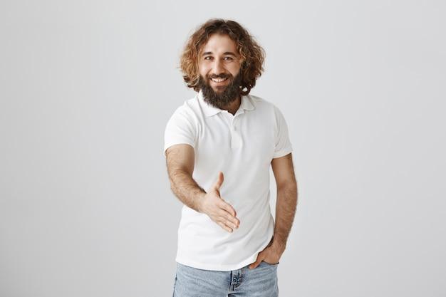 自信を持ってハンサムな中東の男が握手を求めて手を伸ばす