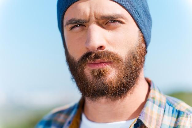 自信を持ってハンサム。屋外に立っているときにカメラを見ているハンサムなひげを生やした男の肖像画