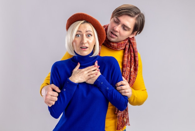 Confident handsome slavic man with scarf around his neck looking at surprised pretty blonde woman with beret putting hands on her chest isolated on white wall with copy space