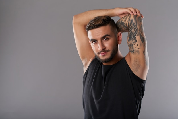 Confident handsome sportsman stretching hands