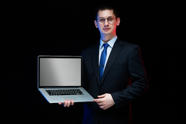 Confident handsome stylish businessman holding laptop in his hands