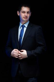 Уверенный красивый стильный бизнесмен с руки на его костюм на черном фоне