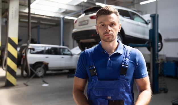 자동차 서비스에서 들어 올려진 자동차의 배경에 대해 포즈를 취한 작업복을 입은 자신감 넘치는 젊고 경험 많은 자동차 수리 노동자