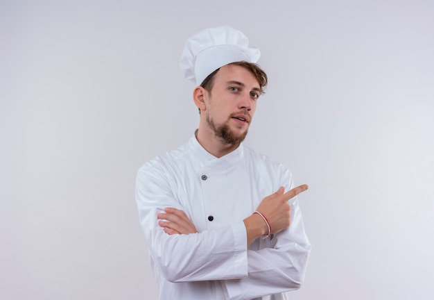 Un bel giovane barbuto chef fiducioso che indossa l'uniforme bianca del fornello e il cappello rivolto verso l'alto mentre guarda un muro bianco
