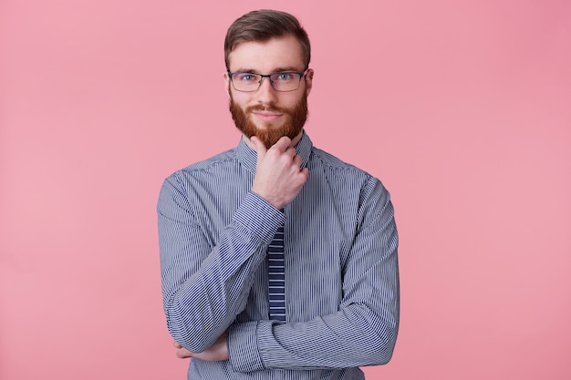 A confident handsome young bearded man in glasses, holds his hand on chin, thinks about something, build a plan, ponders a cool idea. isolated over oink background.