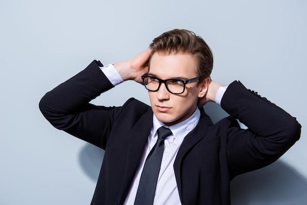 자신감이 잘 생긴 젊은 비즈니스 맨은 순수한 공간에 서서 완벽한 헤어 스타일을 고정합니다. 너무 뜨겁고 매력적이고 거칠고 유행