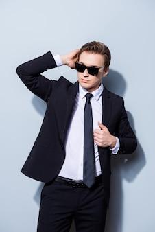 自信を持ってハンサムな若いビジネスマンは、サングラスとスーツの純粋な空間に立って、彼の完璧な髪型を修正しています。とても暑くて魅力的で、過酷でファッショナブルです