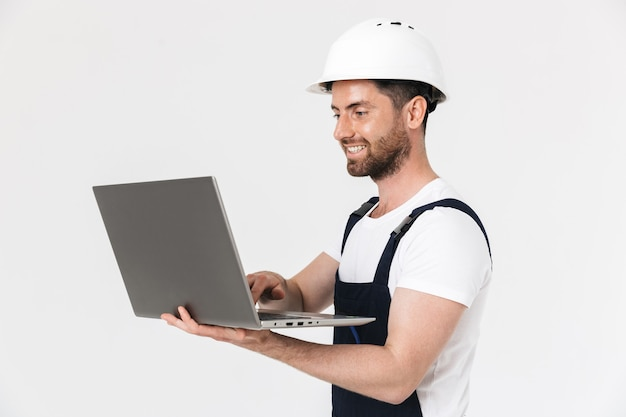 Confident happy bearded builder man wearing overalls and hardhat standing isolated over white wall, using laptop computer