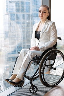 Confident happy businesswoman in wheelchair against the surface of a panoramic window overlooking the skyscrapers and a big city