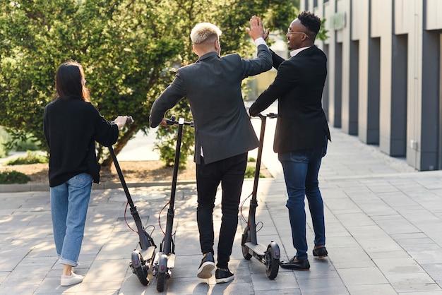 Уверенные, счастливые коллеги из многорасового офиса, обсуждая бизнес-проект, идут рядом с офисным зданием с электрическими скутерами