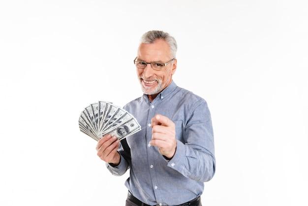 自信を持って幸せな古いビジネスマンを指して、ドルを手で押し