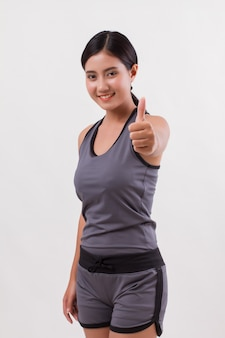 Confident happy smiling fitness woman giving thumb up