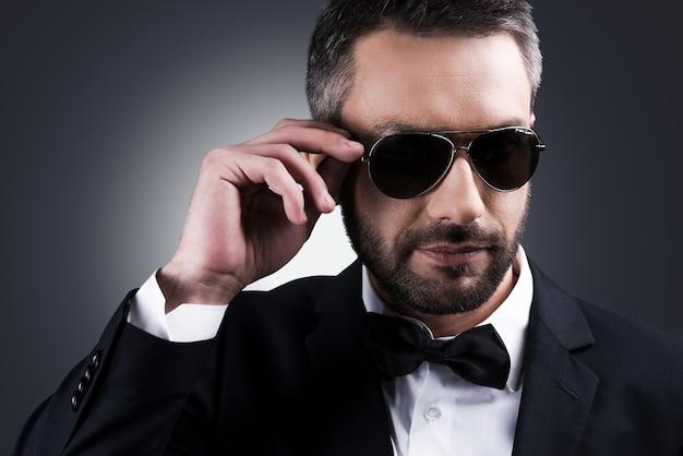 自信のあるハートブレイカー。灰色の背景に立っている間彼のサングラスを調整する正装でハンサムな成熟した男の肖像画