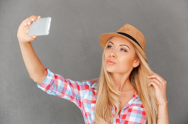 Confident in her beauty. beautiful young woman making selfie on her smart phone
