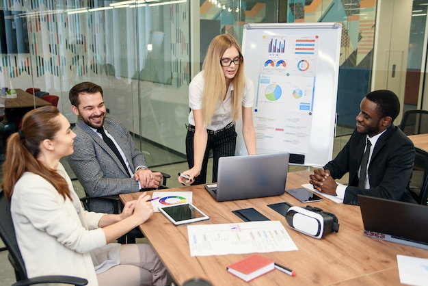 Confident highly-spirited professional multi ethnic team working together with joint business project in meeting room using laptop and reports.