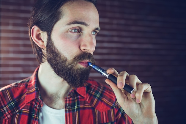 Confident hipster smoking electronic cigarette