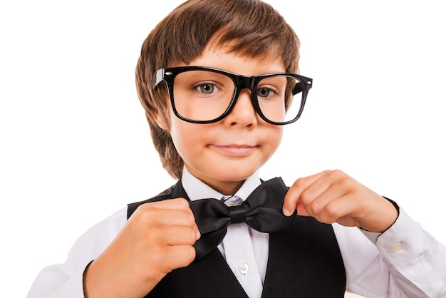 Confident in his skills. cute little boy adjusting his bow tie and looking at camera while standing isolated on white