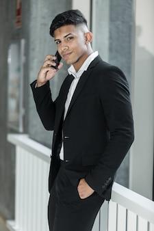 Confident hispanic businessman having smartphone conversation in office